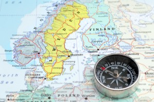 Compass on a map pointing at Norway Sveden and Finland, planning a travel destination in Scandinavia